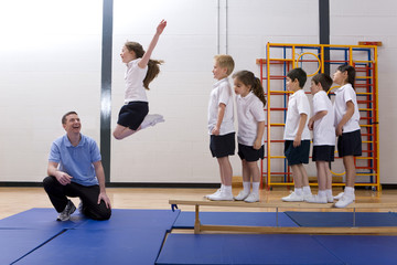 Gym teacher watching school girl jump off bench in school gymnasium