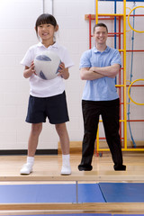 School girl standing on bench and holding ball in school gymnasium with teacher watching