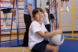 School girl sitting in gymnasium holding ball