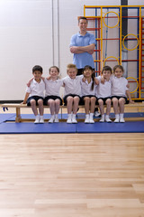 School children and teacher in school gymnasium