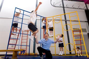 Gym teacher watching school boy jumping off climbing equipment