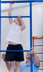 Gym teacher helping student climb gymnasium climbing equipment