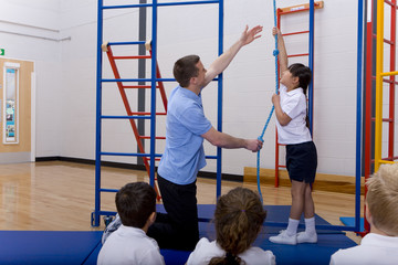 Gym teacher in school gymnasium with students demonstrating rope climbing
