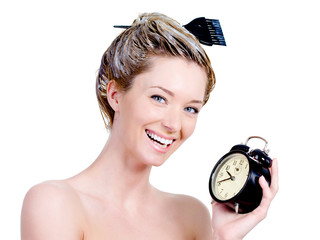 Woman with dye on a hair holding clock