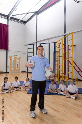Gym teacher in school gymnasium with students