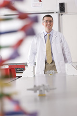 Smiling chemistry teacher standing in school laboratory