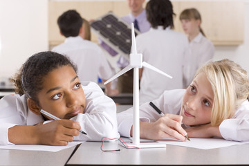 School girls writing report on wind turbines in classroom