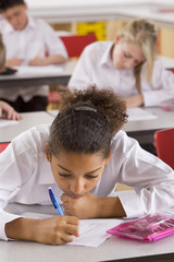 School girl taking test on desk in classroom