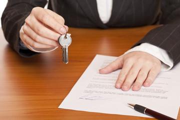 Schlüsselübergabe mit Schlüssel und Mietvertrag in Händen