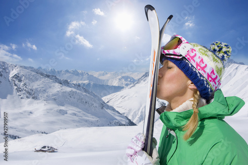 Woman kissing skis on snowy mountain