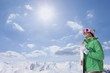 Sun shining above happy woman wearing goggles and holding skis on snowy mountain