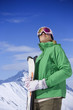 Happy woman wearing goggles and holding skis on snowy mountain