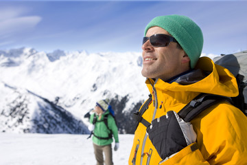 Couple with backpacks enjoying sunshine on snowy mountain