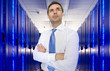Businessman with arms crossed looking up in network server room