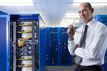 Portrait of confident businessman in network server room