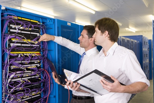 IT technicians checking LAN cables on network server