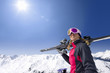 Smiling woman holding skis on snowy mountain under sun in blue sky