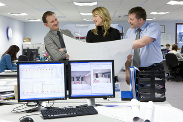 CAD designer and architects viewing blueprints in office