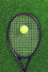 Tennis raquet and ball on grass