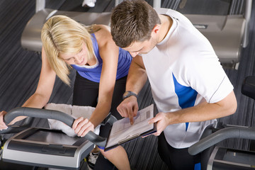Personal trainer and woman on exercise bike looking at clipboard in health club