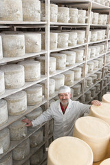 Portrait of smiling cheese maker in cellar with aged and young farmhouse cheddar cheese wheels
