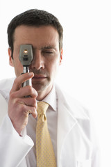 Ophthalmologist peering through ophthalmoscope