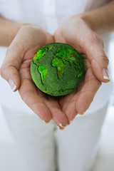 Woman carefully holding grass-covered globe