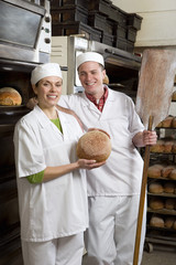 Bakers with peel and loaf standing next to oven