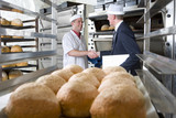 Inspector shaking hands with baker in bakery