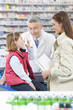 Daughter taking asthma inhaler as mother and pharmacist watch