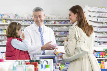 Pharmacist talking to mother about cold medicine in pharmacy