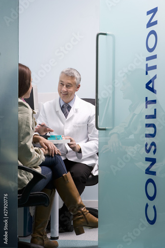 Pharmacist consulting with customer about medication