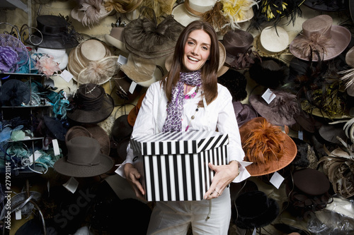 Saleswoman holding hat box in front of wall of ornate hats in shop