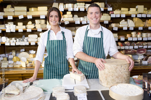 Salespeople standing at counter with cheese in cheese shop