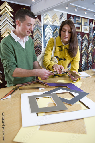 Salesman helping customer in frame shop