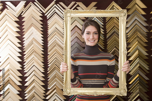 Clerk lifting gold frame in frame shop