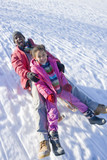 Excited father and daughter sledding down snowy hill on sled