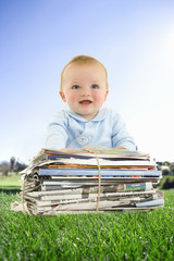 Baby sitting in grass with bundle of newspapers