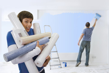 Woman carrying armful of wallpaper while husband paints
