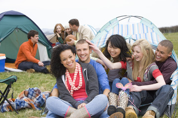 Happy couples camping in tent and attending outdoor festival