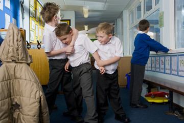 Aggressive school boys rough housing in classroom