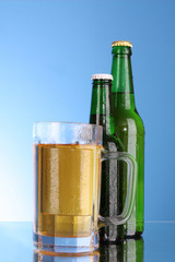 Bottles with beer and cup on blue background