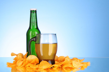 Bottles with beer, cup and potato chips on blue background