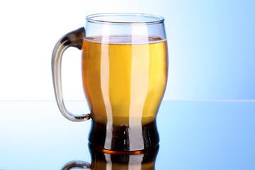 Mug of beer on blue background