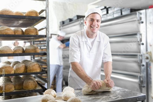 Baker kneading bread dough in bakery