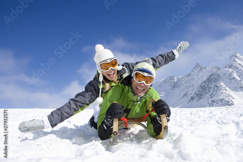 Couple laying on sled in snow on mountain top