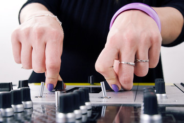 Hands of female DJ playing