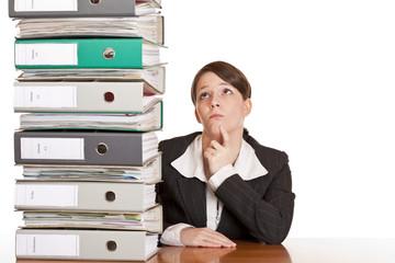 Frau denkt im Büro nach Lösung, um Ordnerstapel zu beseitigen