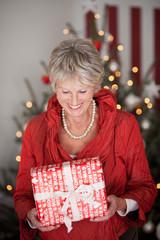 glückliche seniorin mit weihnachtsgeschenk