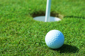 Golf ball on green grass in front of hole